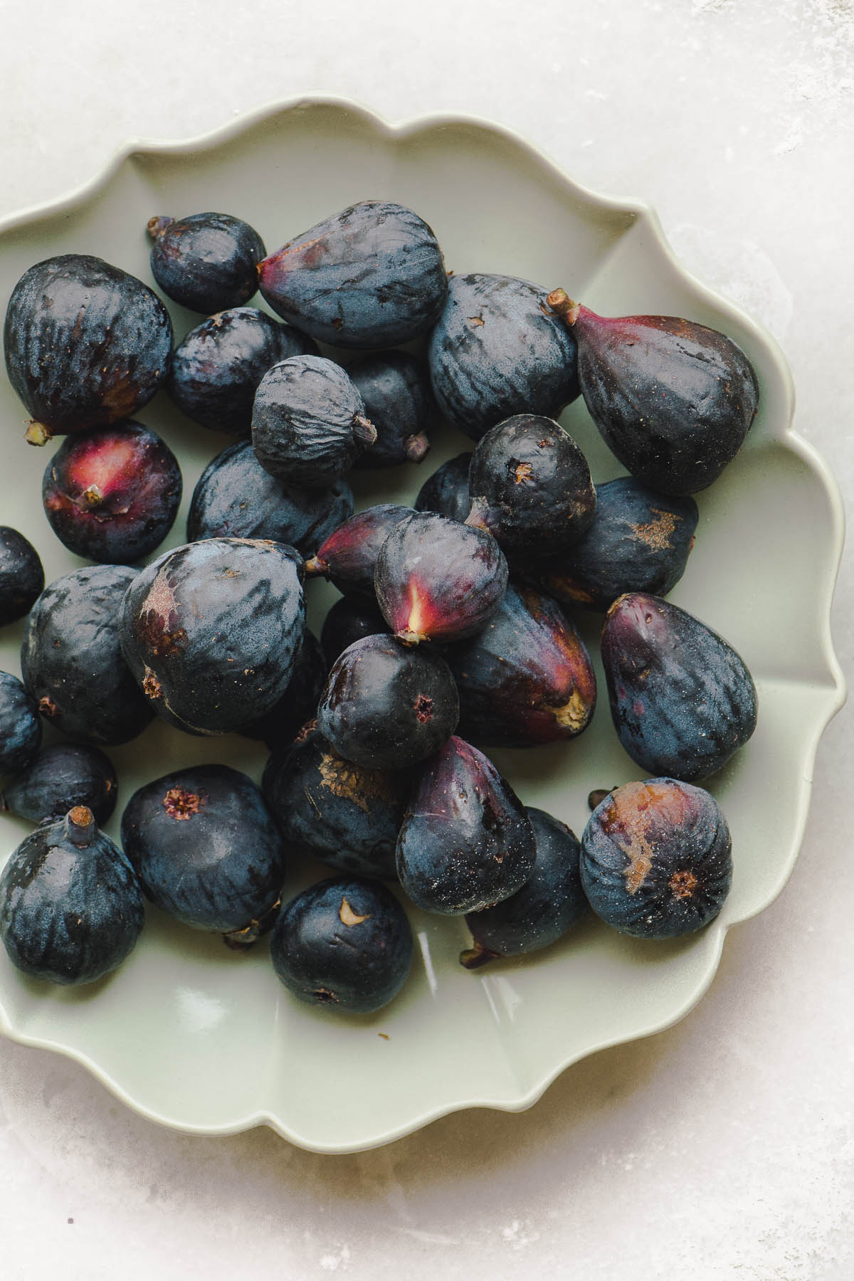 Black Mission figs in a green bowl ready to be sliced for a fig tart with lavender honey