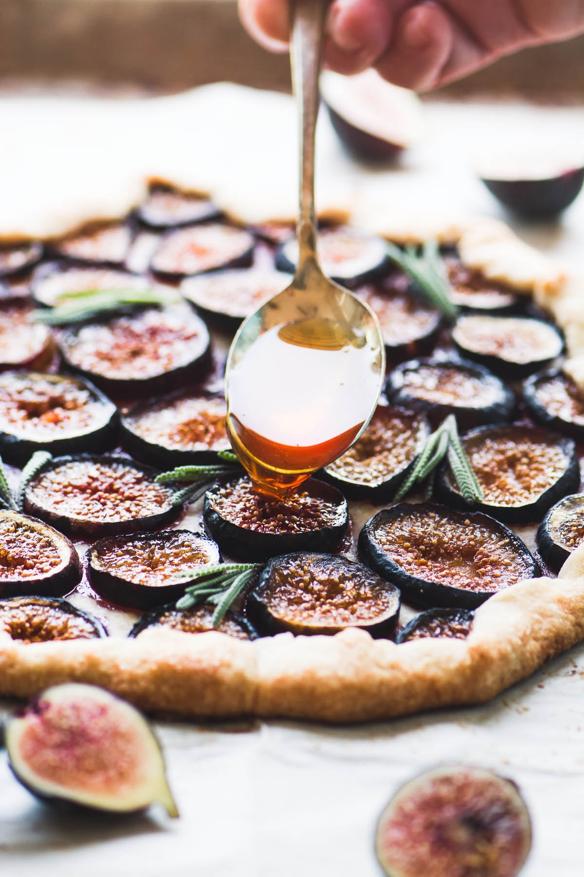 Spooning honey over a fig tart with lavender honey