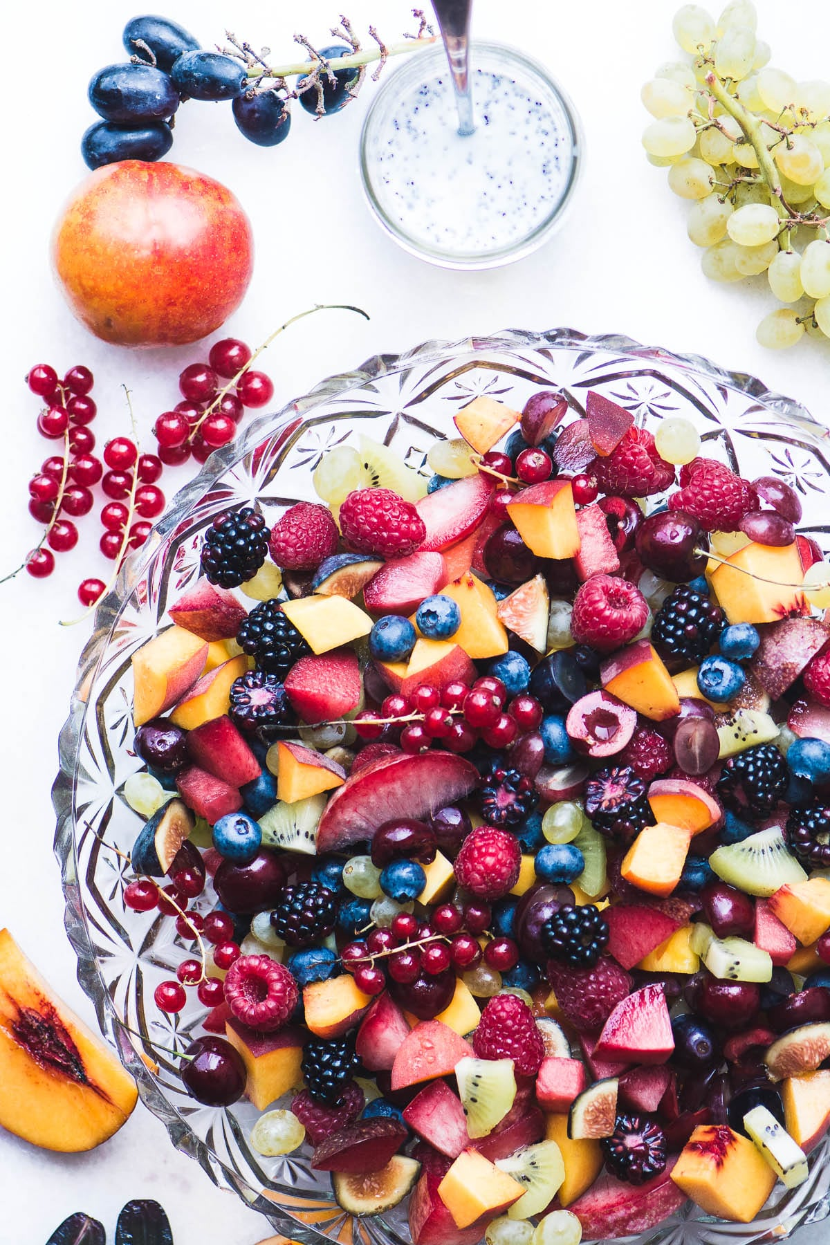 Summer fruit salad in a glass bowl with kefir poppy seed dressing