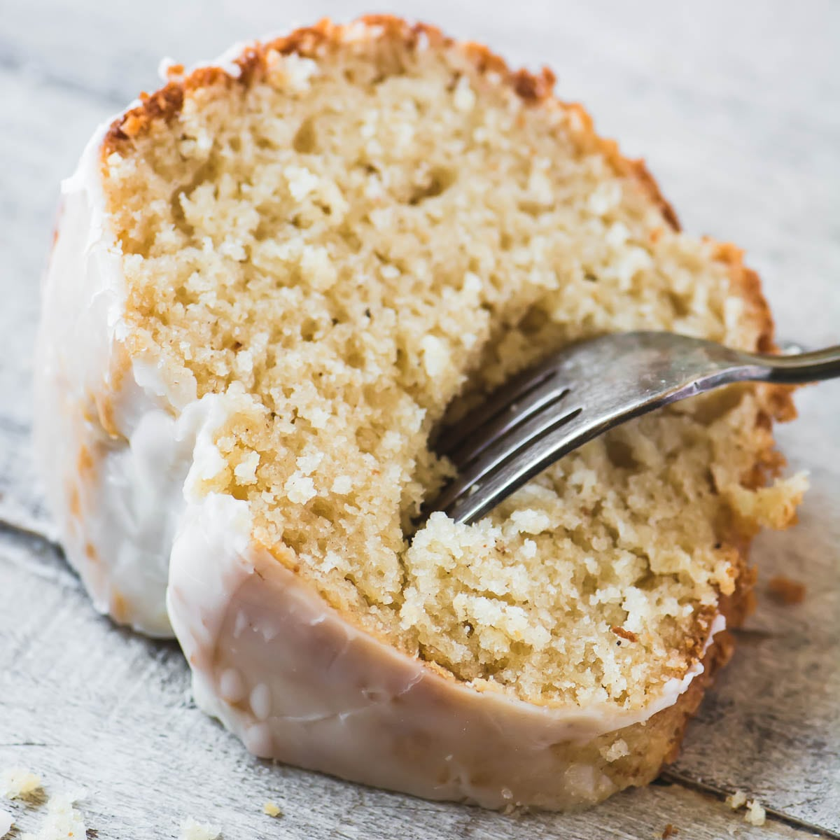 A slice of Glazed Old Fashioned Doughnut Bundt Cake with a fork