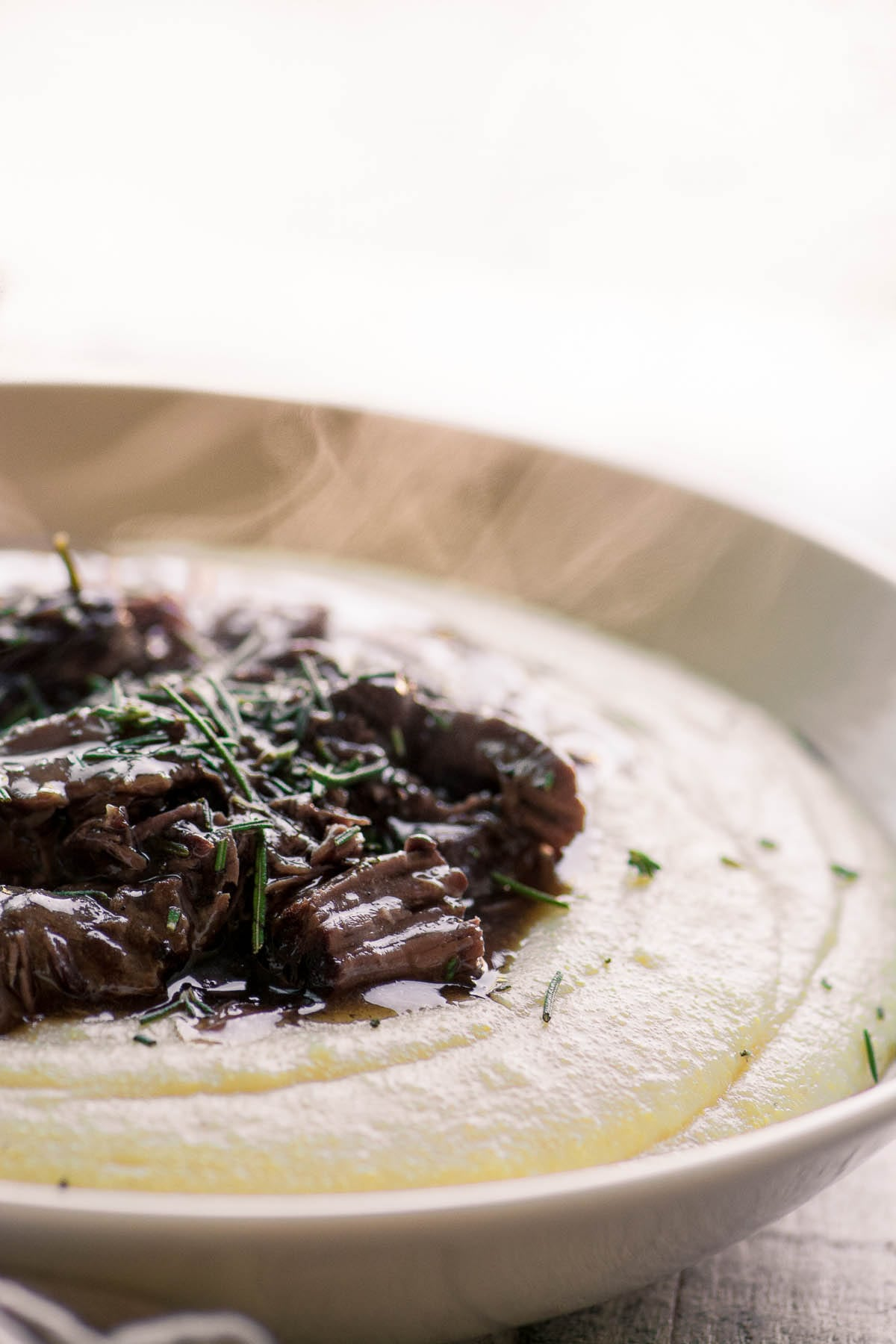 A bowl of Instant Pot Short Ribs over polenta in a bowl