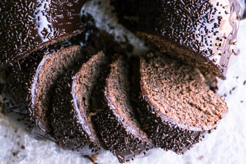 Chocolate Sour Cream Doughnut Bundt Cake, sliced, with sprinkles on parchment paper