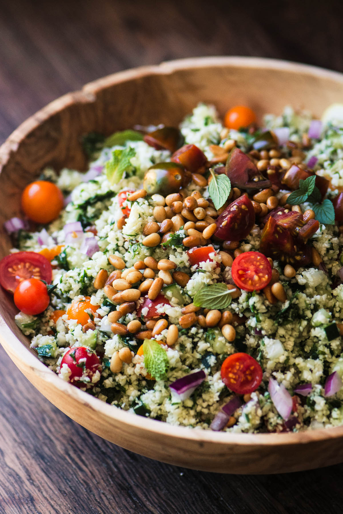 cauliflower rice tabbouleh in a wooden bowl topped with toasted pine nuts