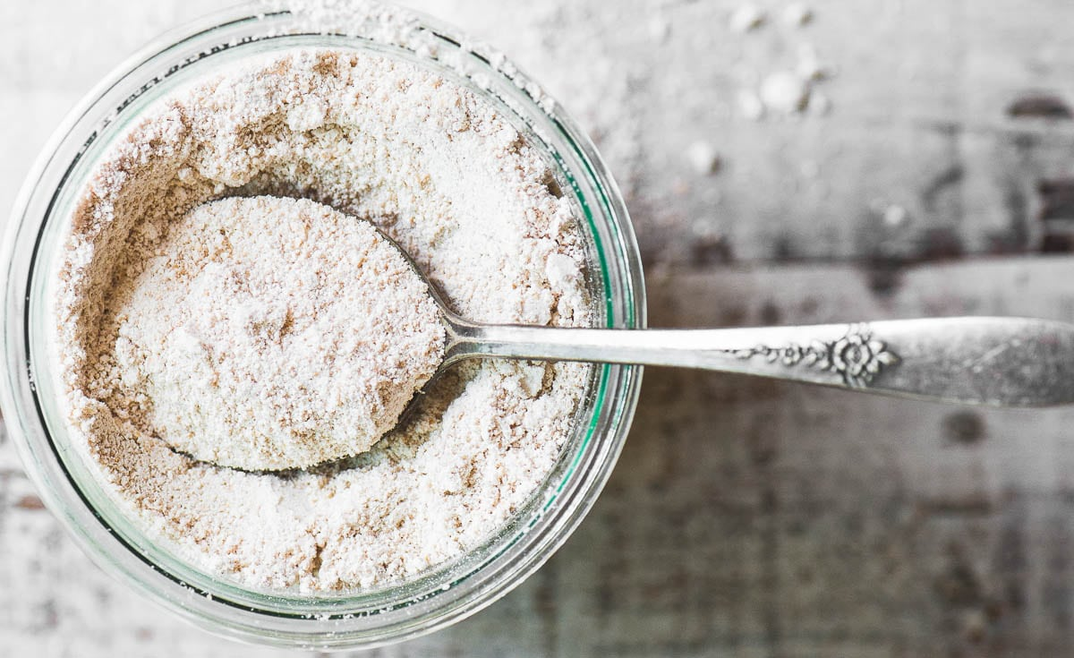 Homemade Oat flour in a glass jar with spoon