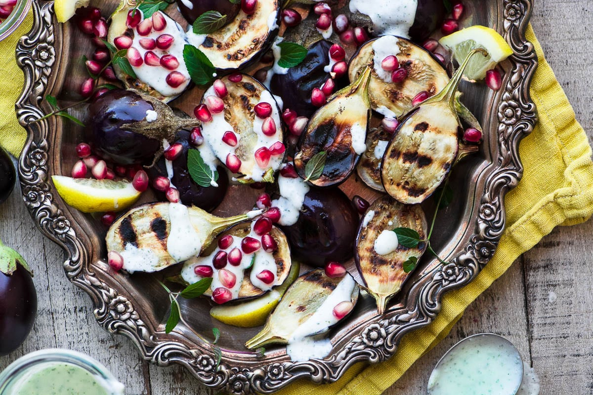 Grilled Baby Eggplant with Minted Yogurt and Pomegranate on a silver platter