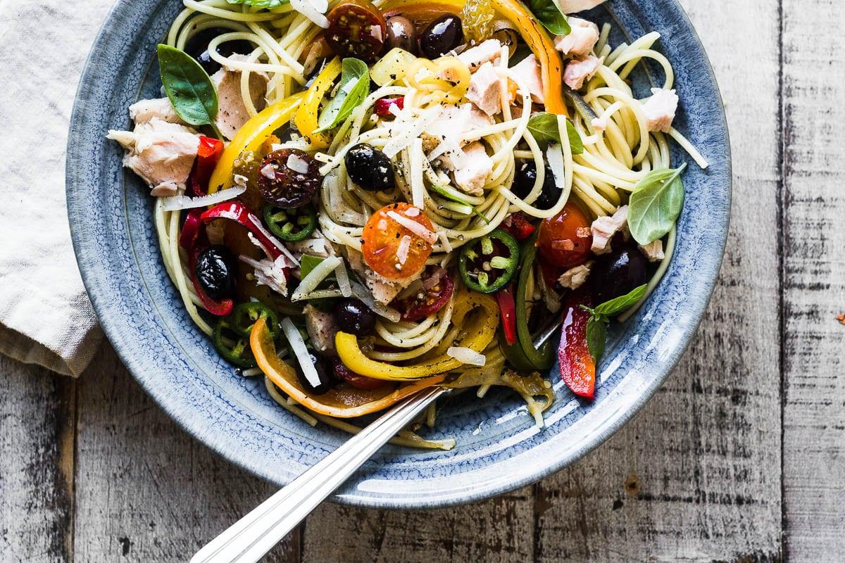 Spaghetti Peperonata with tuna and olives in a blue bowl