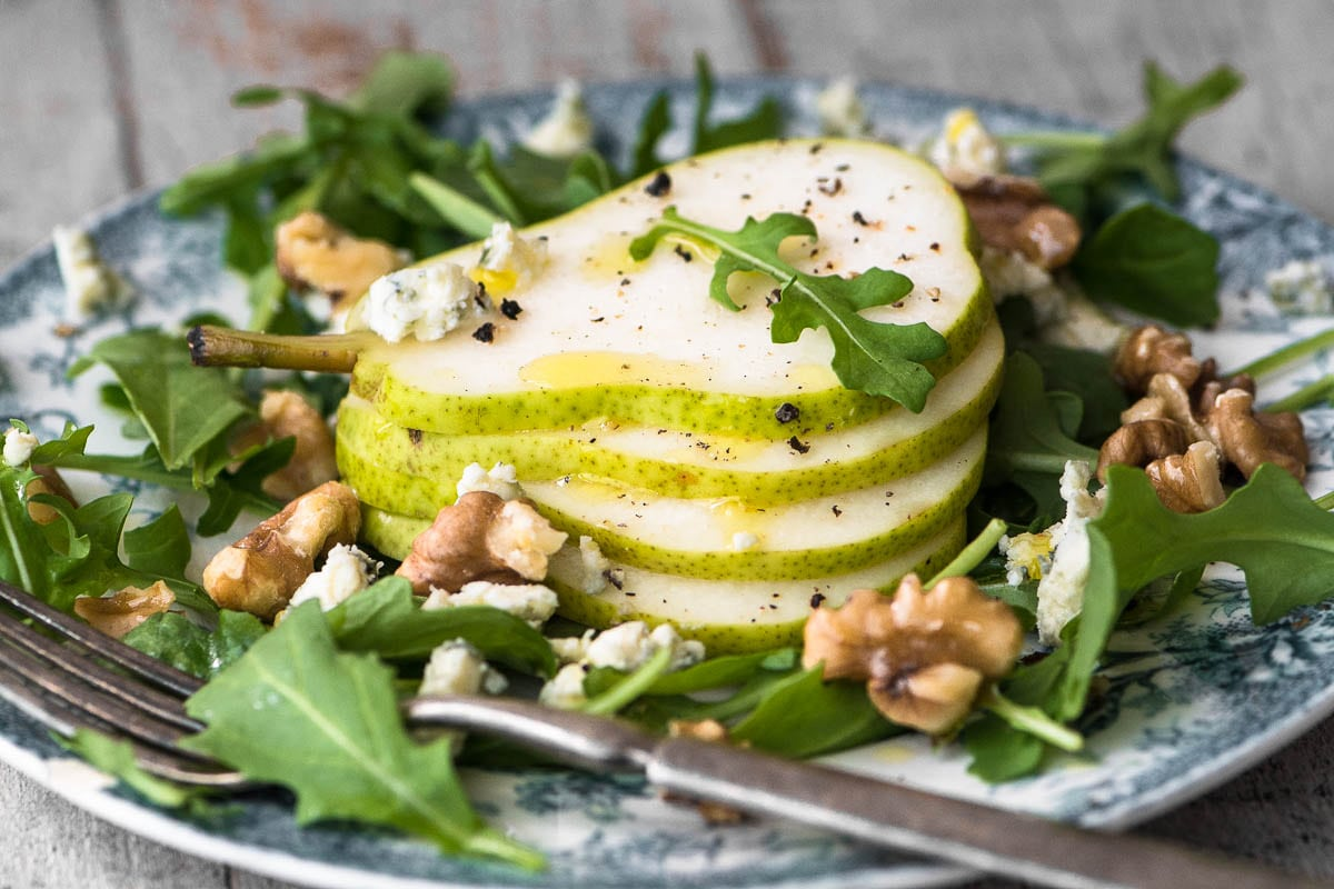 A plate of pear salad with creamy walnut vinaigrette
