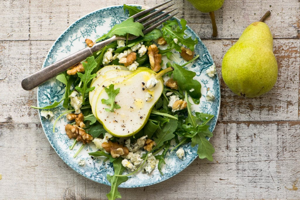 A pear salad with creamy walnut vinaigrette on a wooden table with green pear