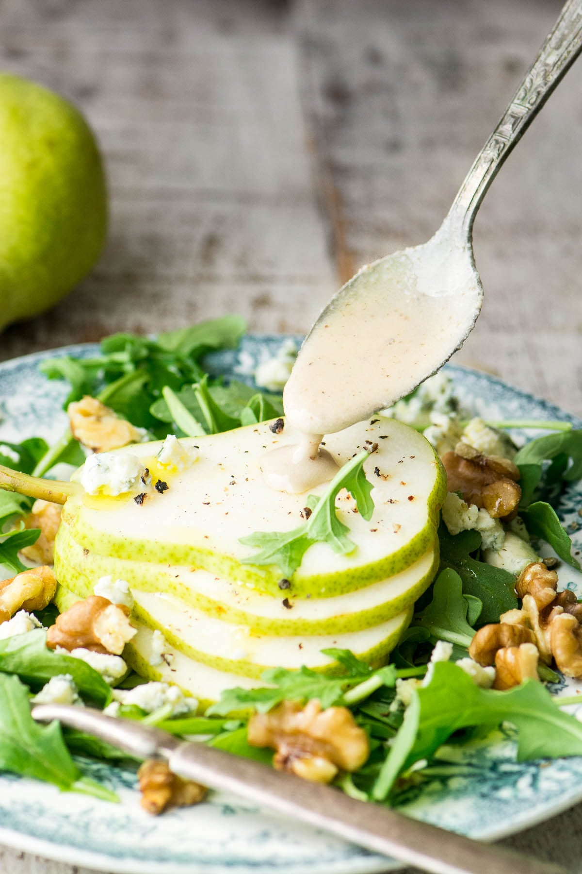 Spooning dressing over Pear Salad with Creamy Walnut Vinaigrette