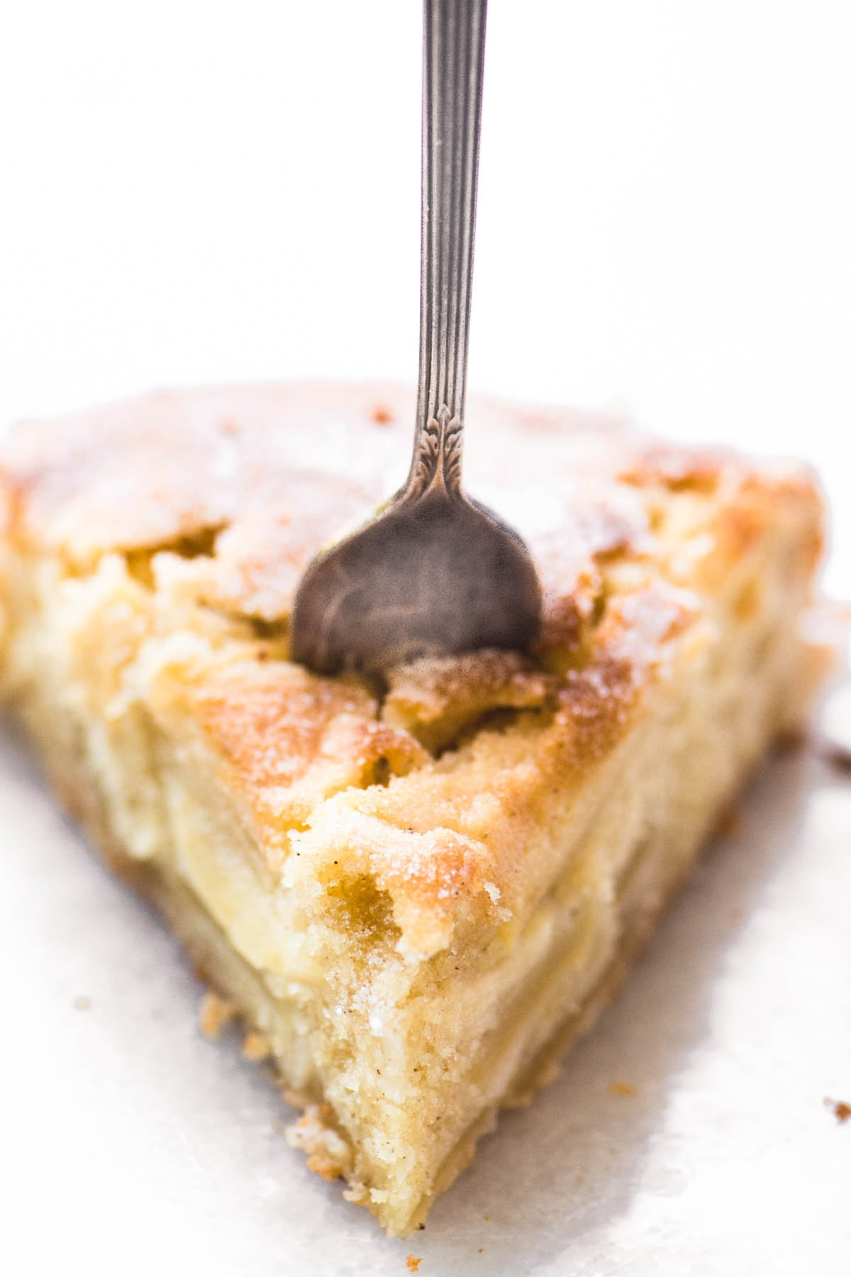 A slice of Dutch Apple Cake with a fork stuck into it.