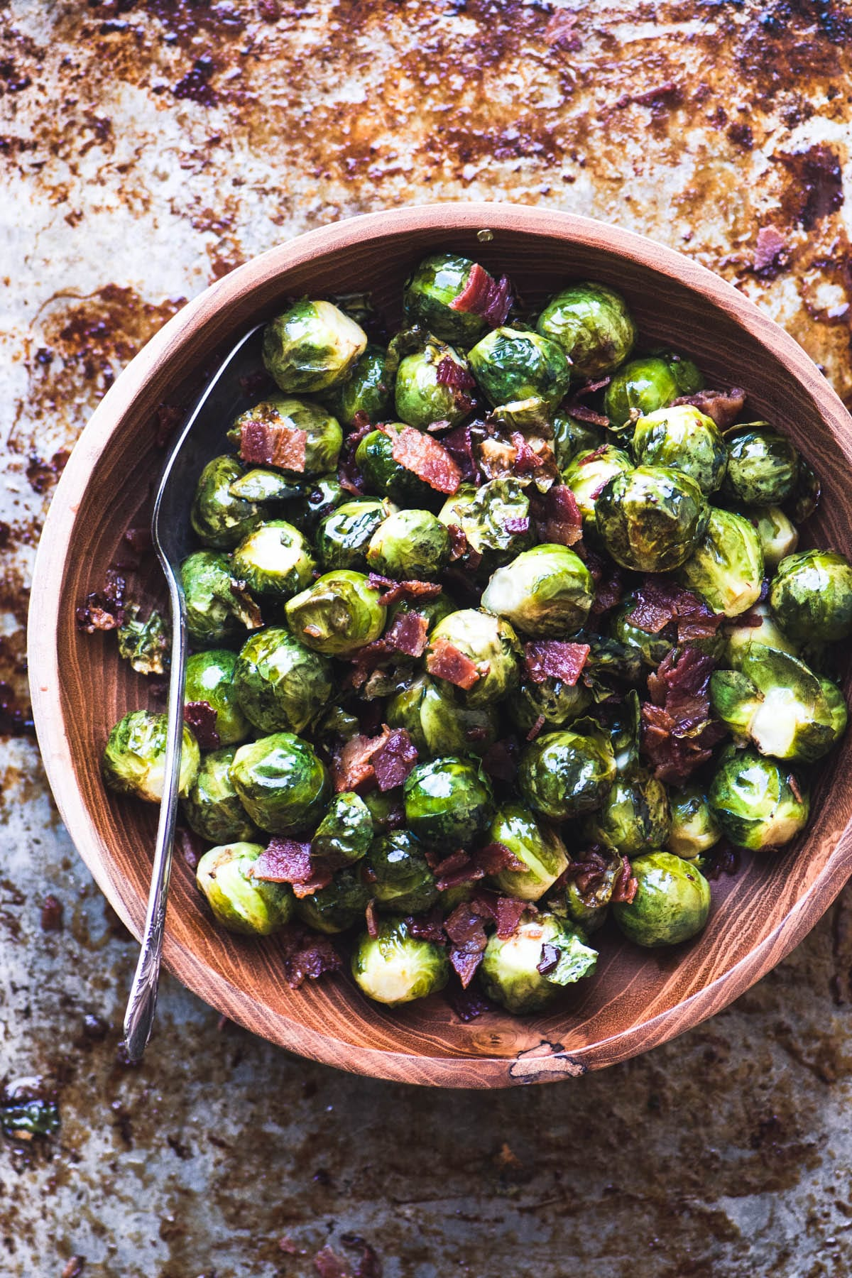 A wooden bowl filled with Maple Candied Brussels Sprouts with bacon