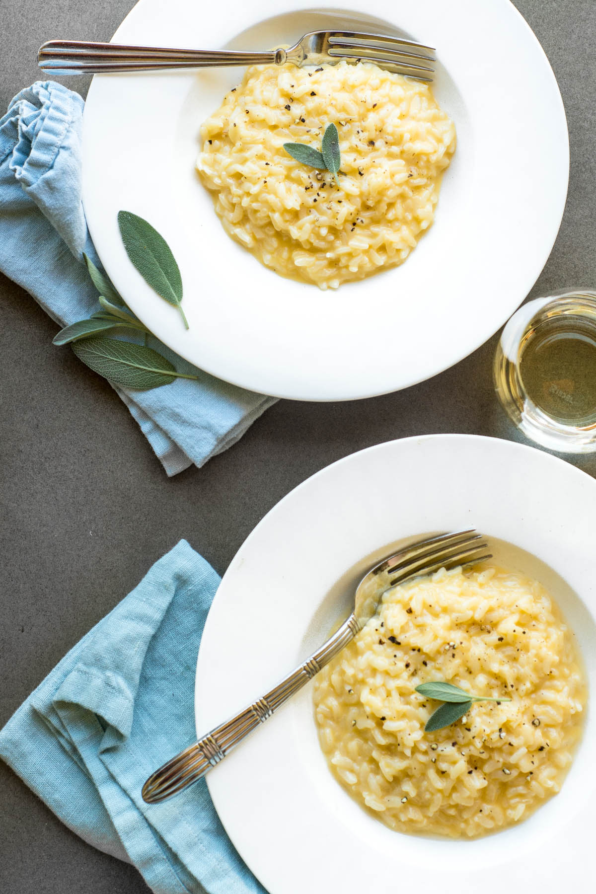 Cheddar risotto with fresh sage in white bowls with blue napkins