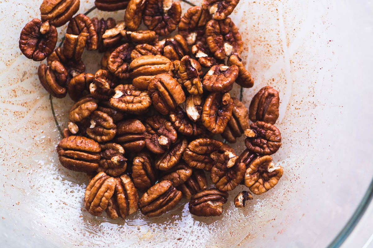 Making Maple spiced pecans in a glass bowl
