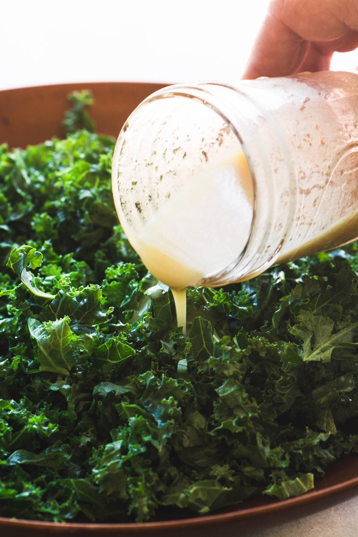 Dressing a Kale and Butternut Squash Salad with a maple cider vinaigrette