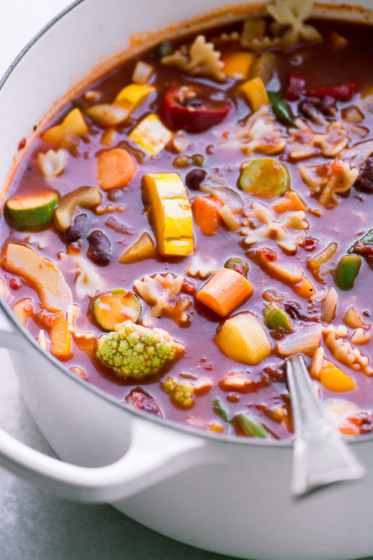 Bright and colorful minestrone soup in a white pot