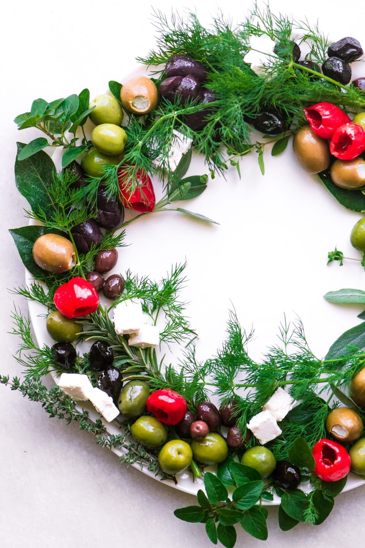 Olive and herb wreath appetizer on a white platter on a marble surface