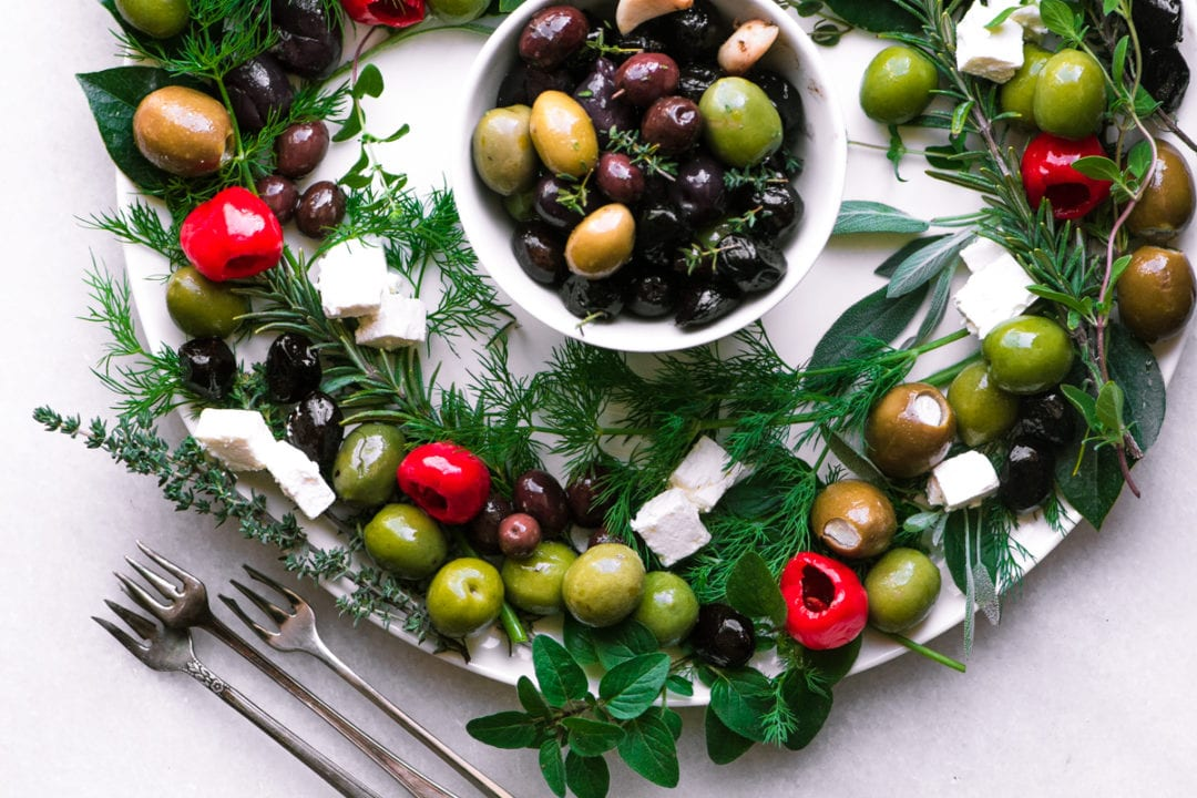 Olive and Herb Appetizer Wreath on a white platter with cocktail forks