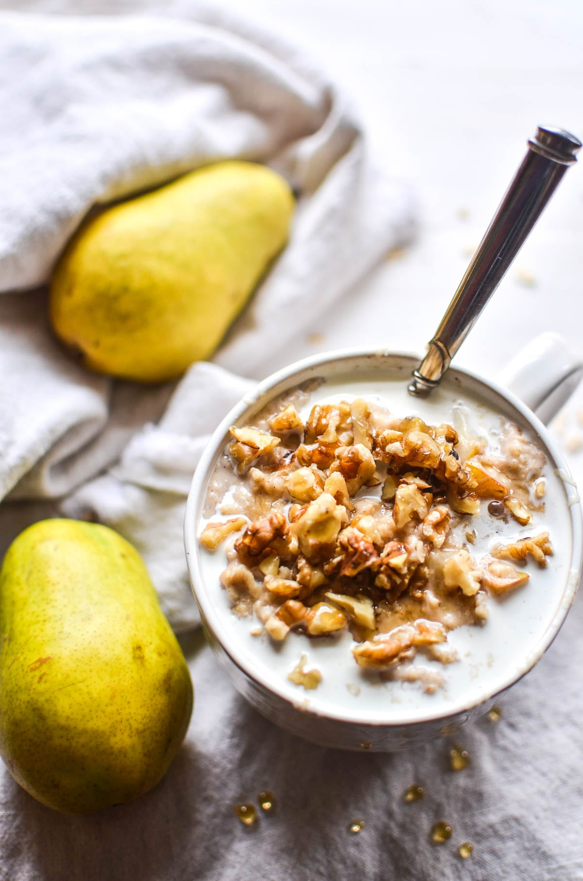 A bowl of spiced pear oatmeal with pears on a white ground
