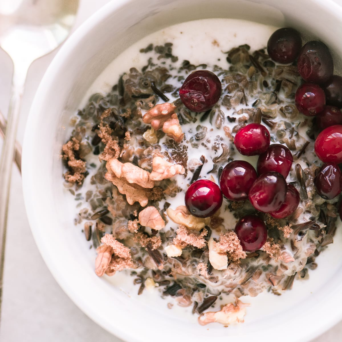A bowl of wild rice porridge with cranberries and walnuts