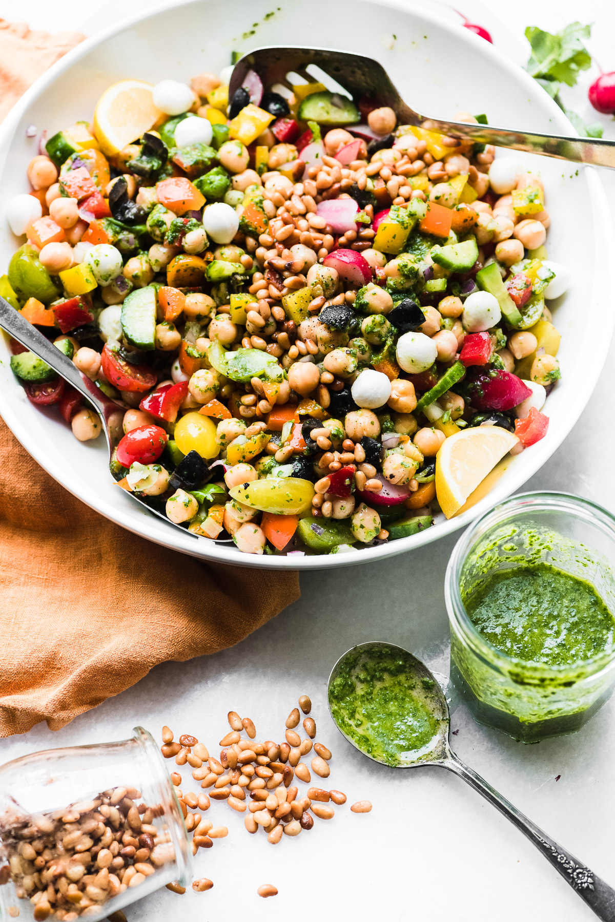Healthy Chickpea Salad with Pesto with napkin, jar of pesto, and pine nuts