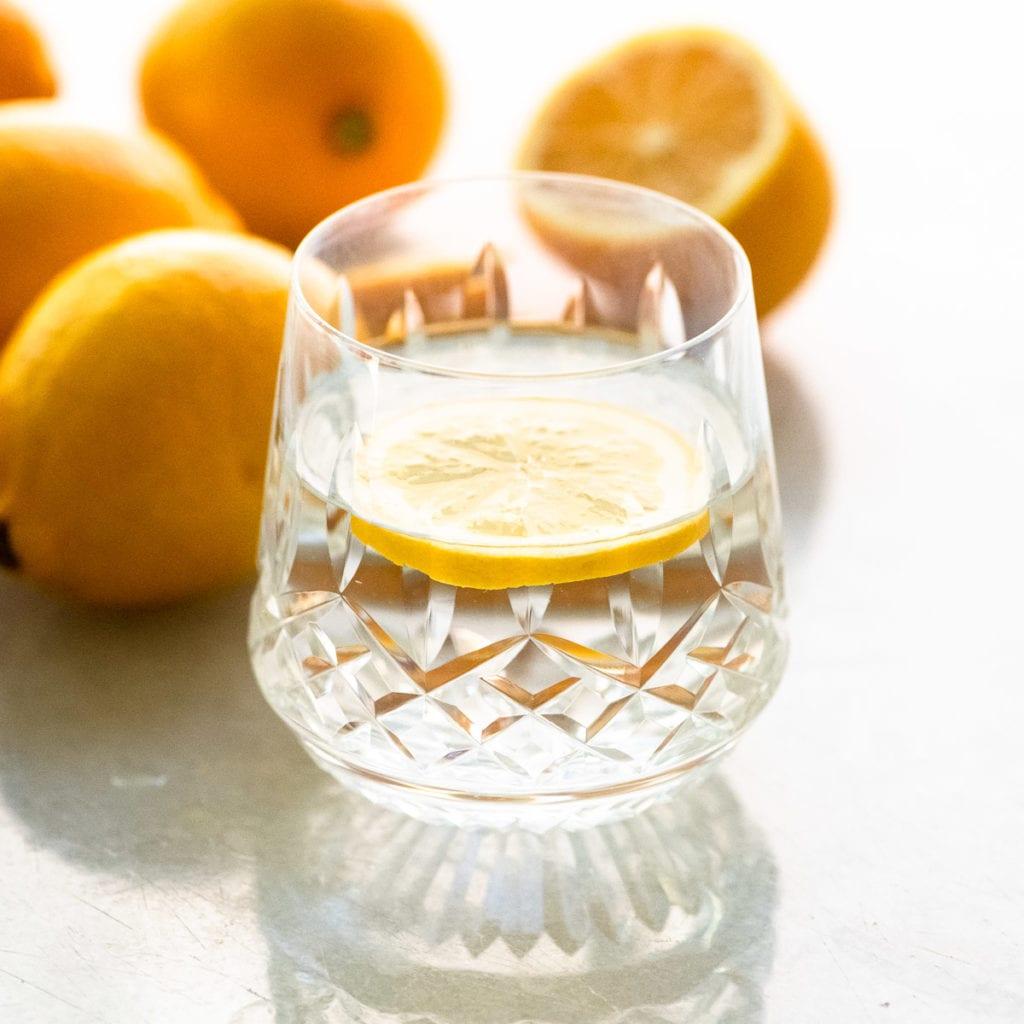 A glass of lemon water with whole lemons