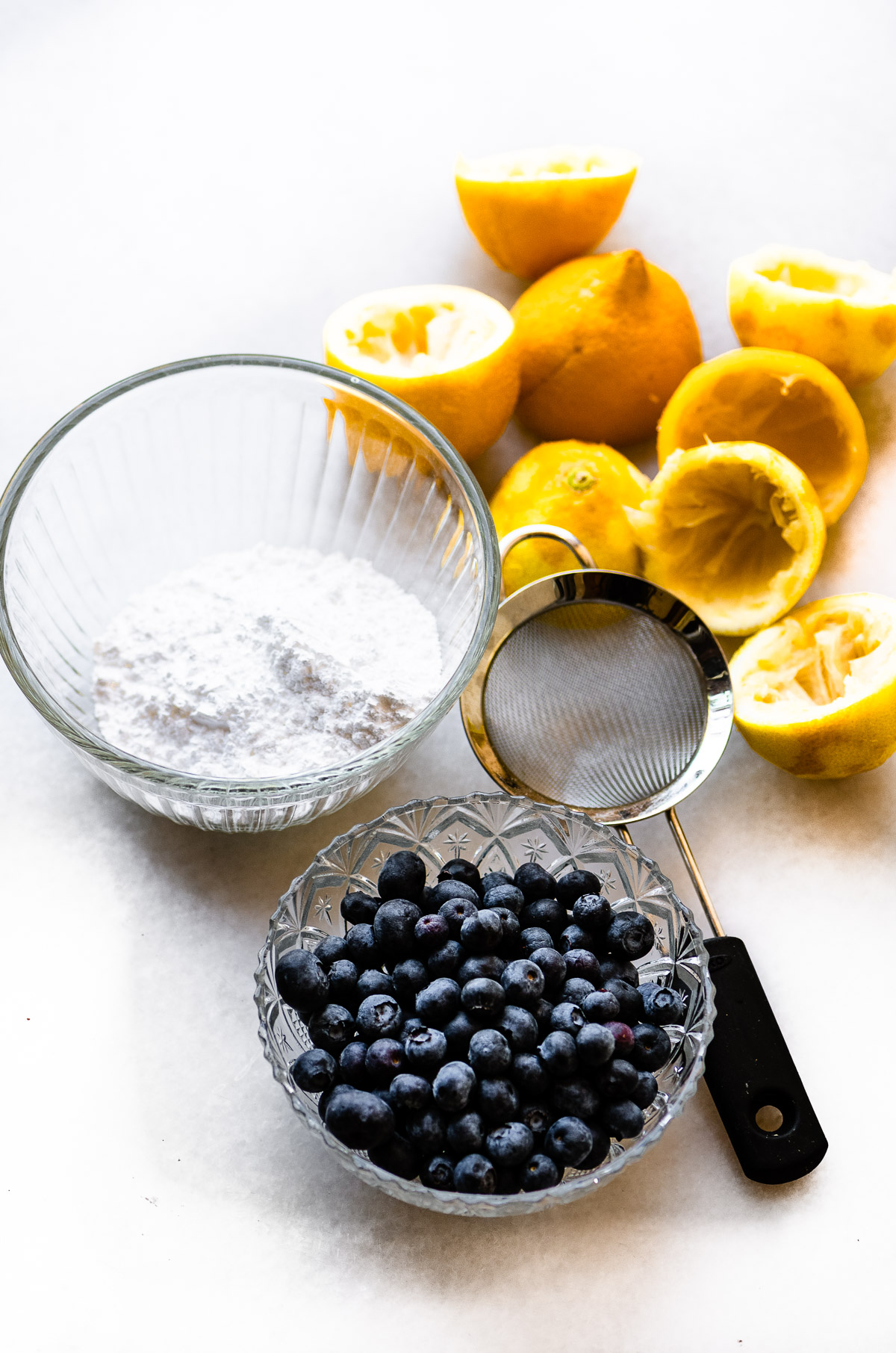 lemons, blueberries, and powdered sugar for a flourless warm lemon pudding cake recipe