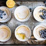 Warm lemon puddings on a baking sheet with blueberries