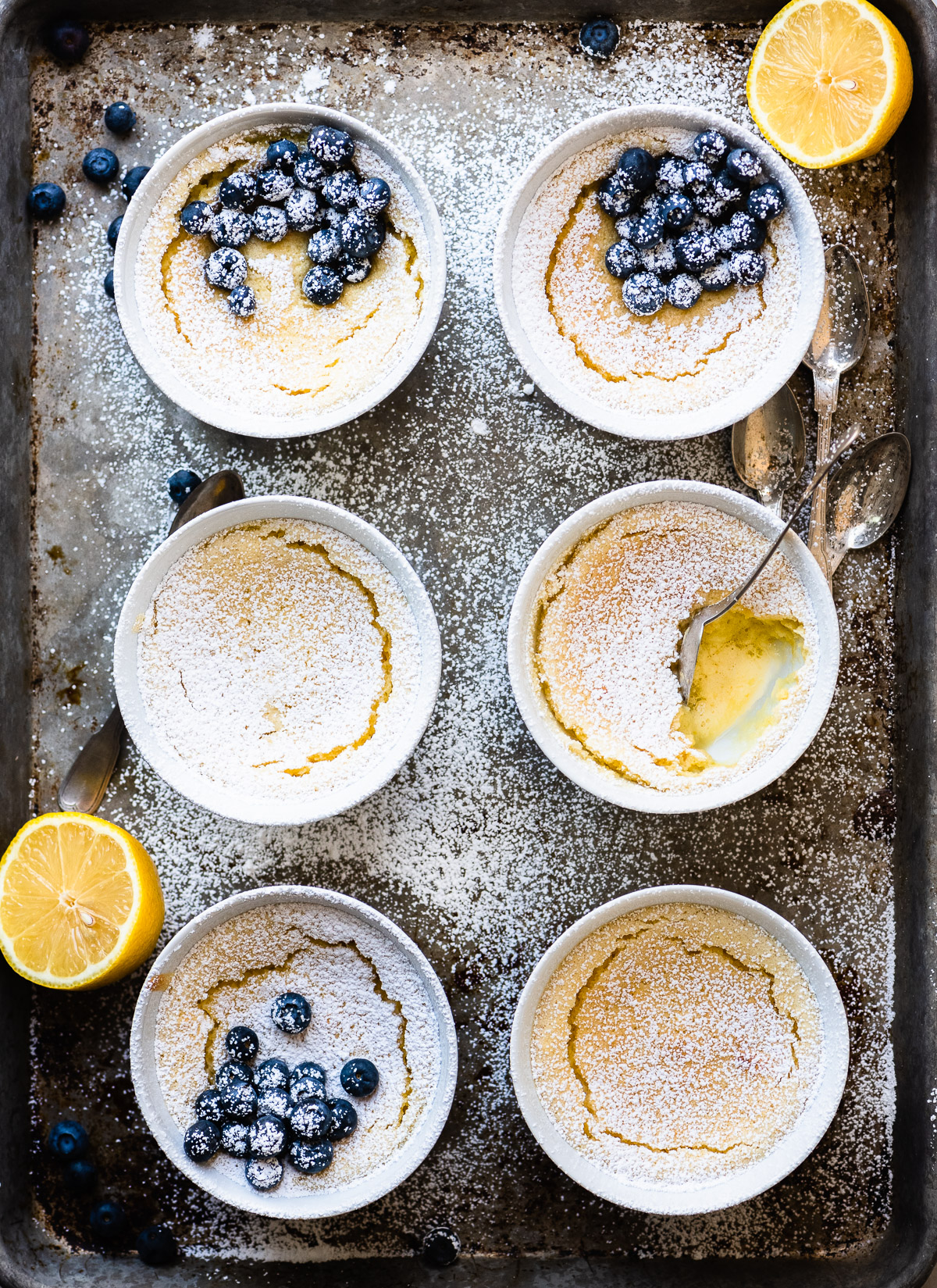 flourless warm lemon pudding cakes on a baking sheet with lemons and blueberries