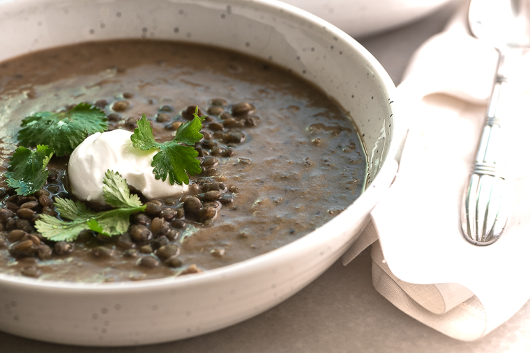 Lentil and Bone Broth soup garnished with yogurt and cilantro