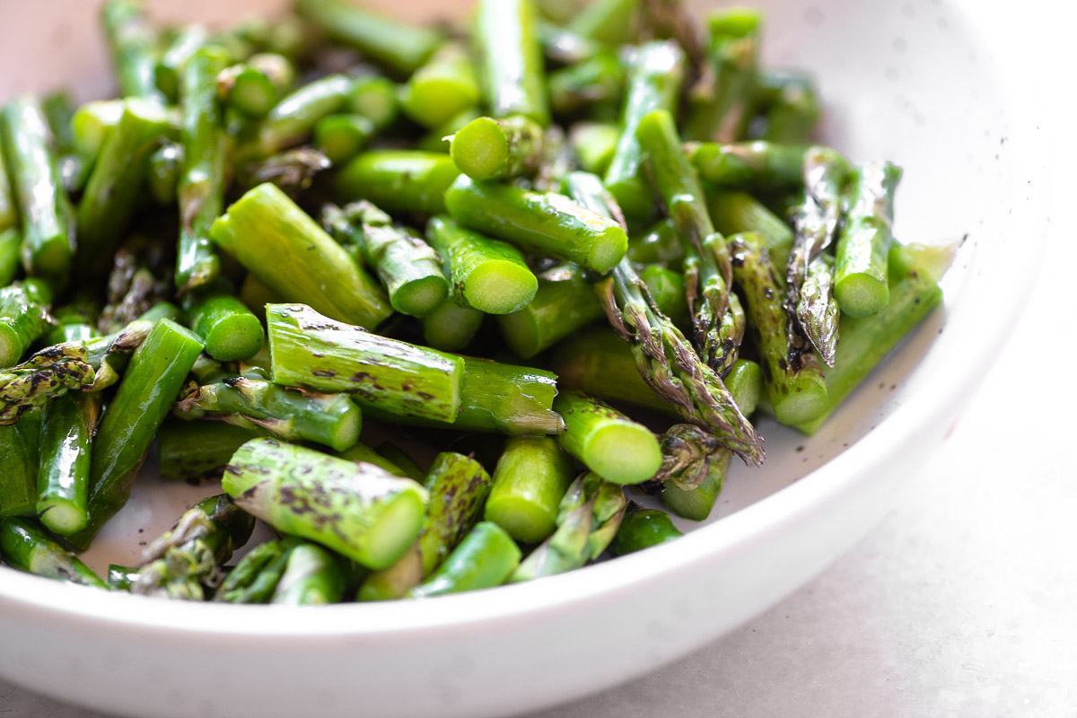 A bowl of blistered asparagus, chopped