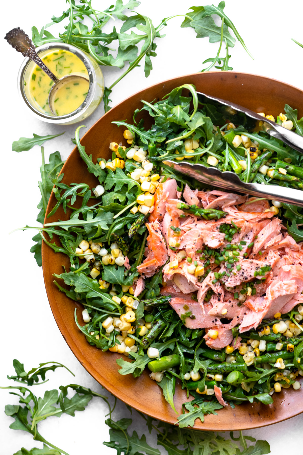 Blistered corn and asparagus salad with salmon in a wooden bowl