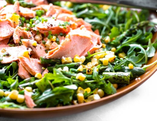 Blistered corn and asparagus salad with salmon in a wooden bowl, side view