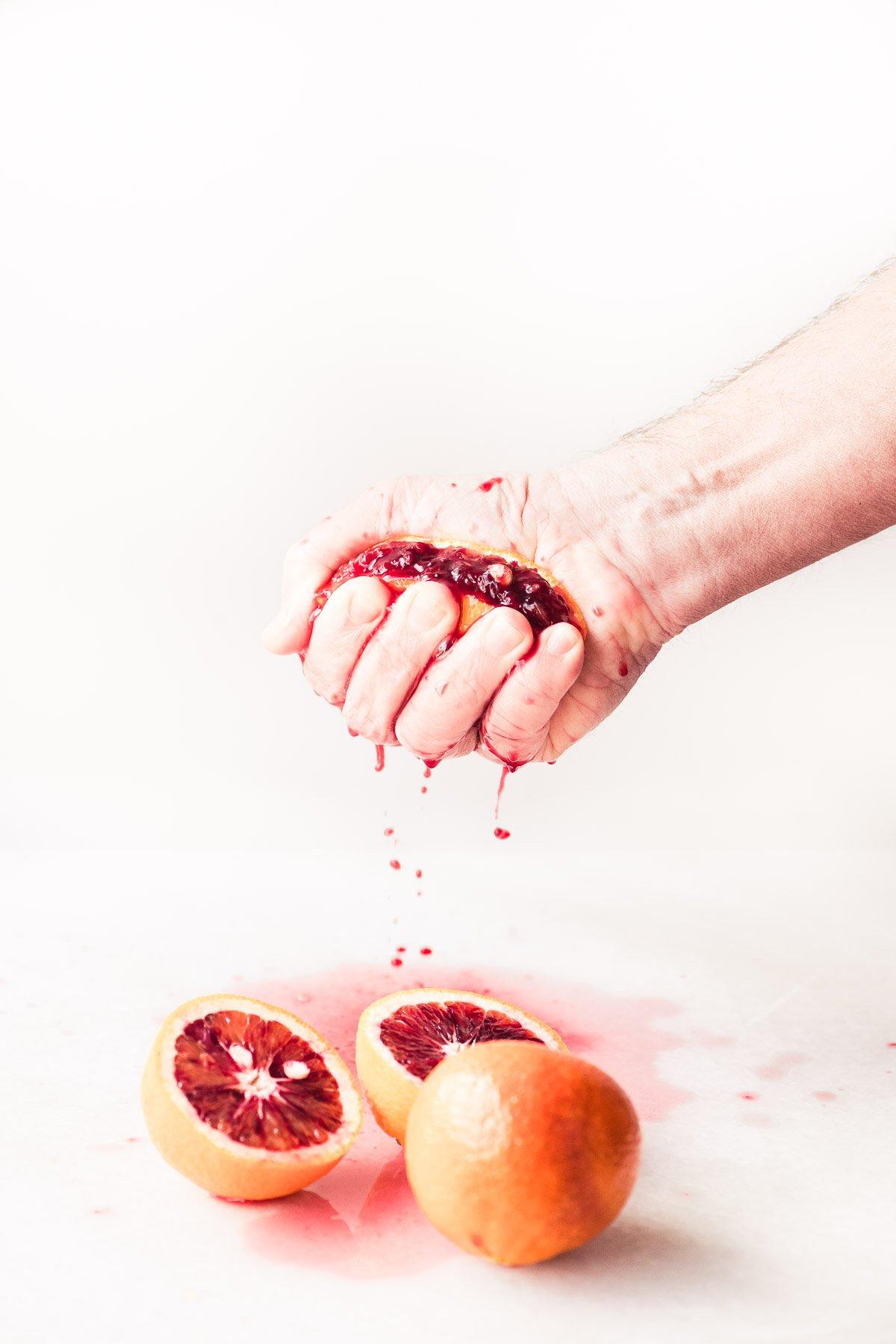 squeezing a blood orange for a blood orange spremuta