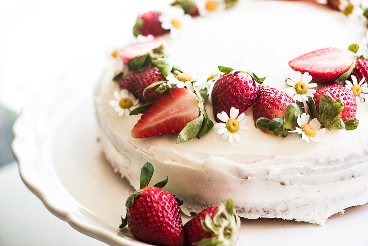 An Easy Strawberry Cake On A White Stand With Fresh Strawberries