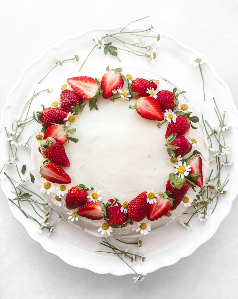 An easy strawberry cake with flowers on a white platter
