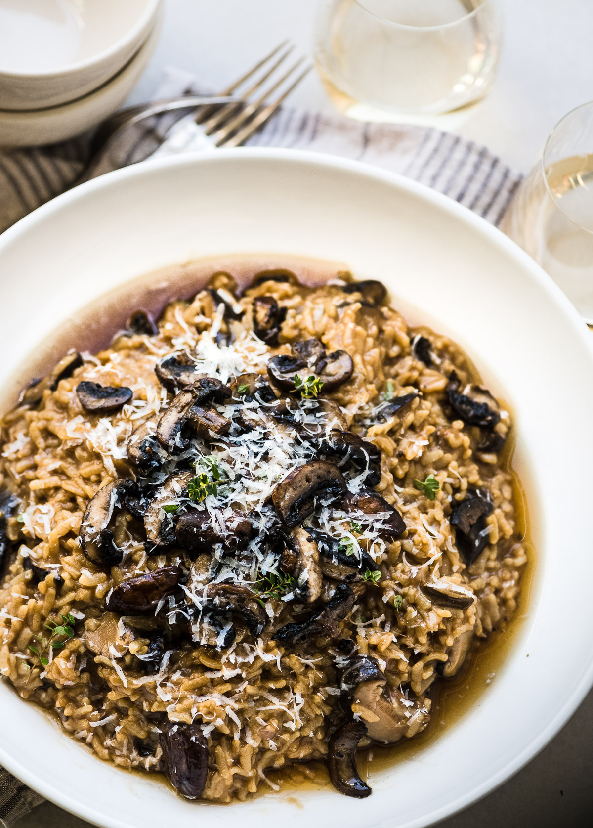 Instant Pot Wild Mushroom Risotto in a white bowl with wine