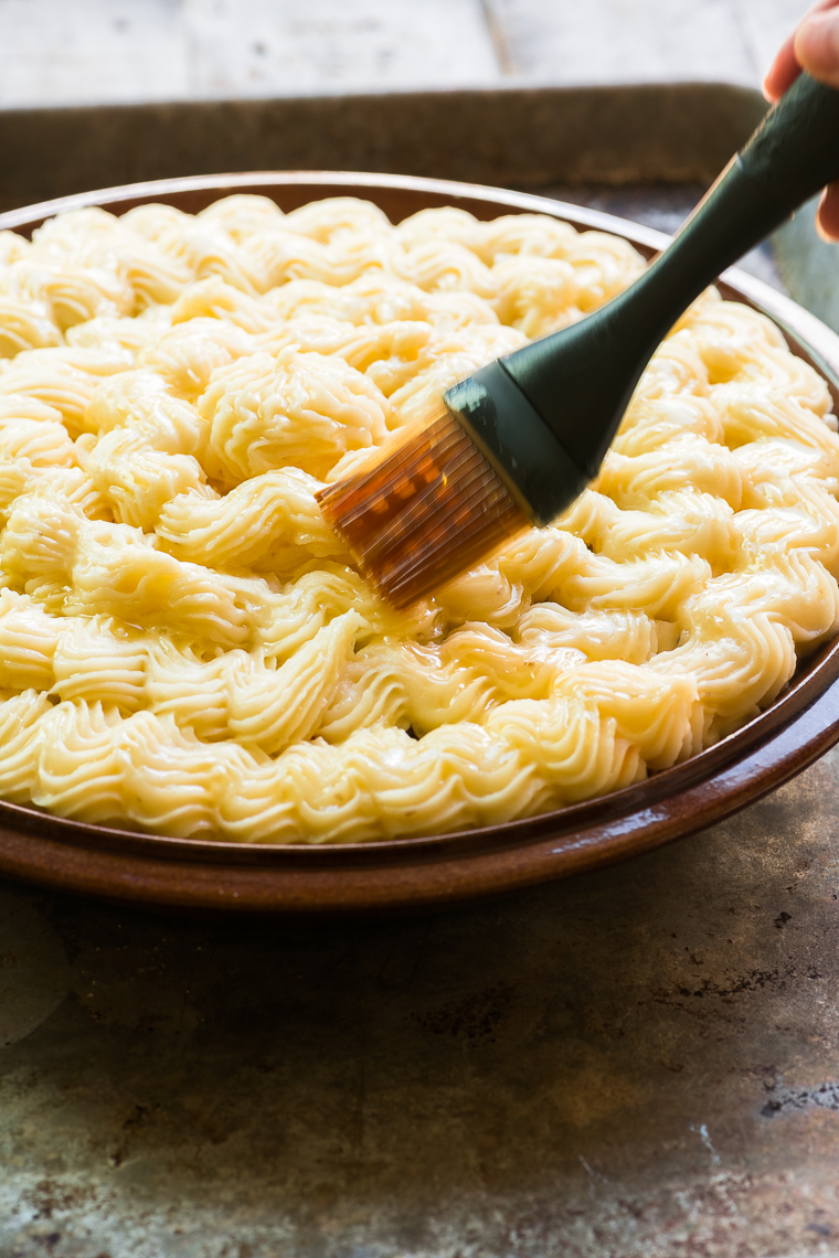 Brushing melted butter on the top of a cottage pie