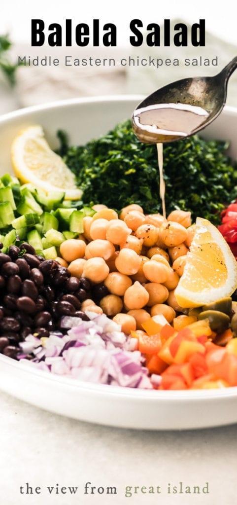 Spooning dressing on Middle Eastern Balela Salad