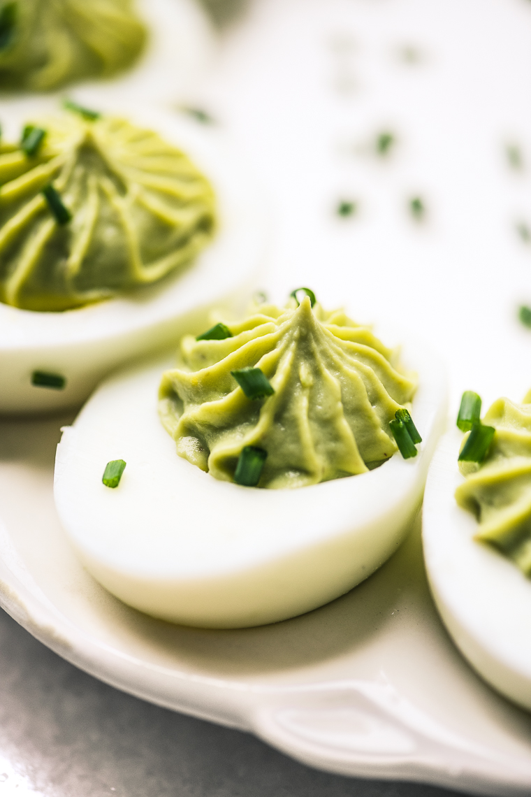 Guacamole Deviled Eggs on a white tray with snipped chives on top