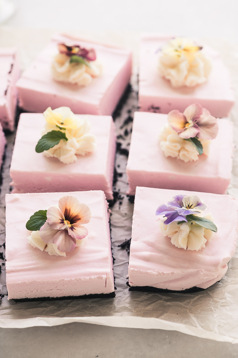 No Bake Black Bottom Strawberry Cheesecake Squares garnished with pansies