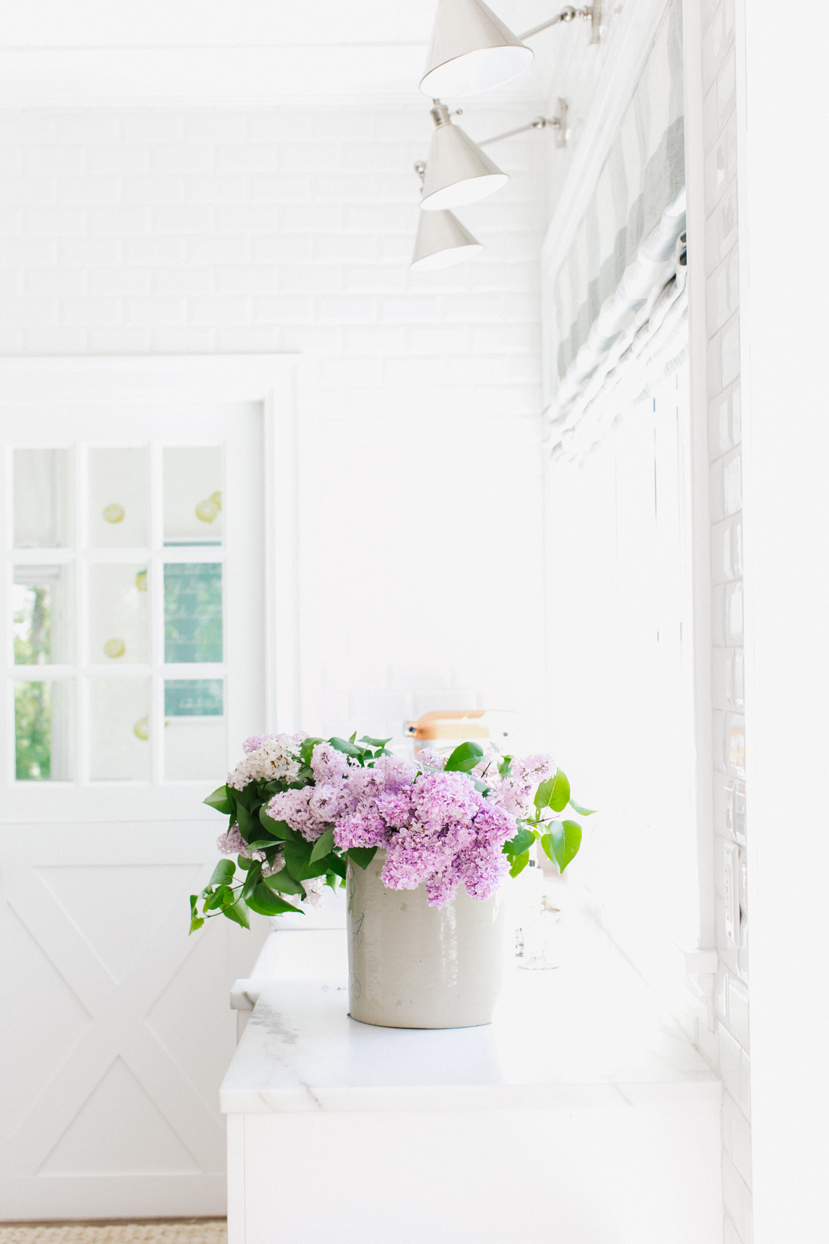 Large crock with lilacs on a white countertop.
