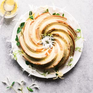 Orange Blossom Bundt Cake on a white plate with white flowers