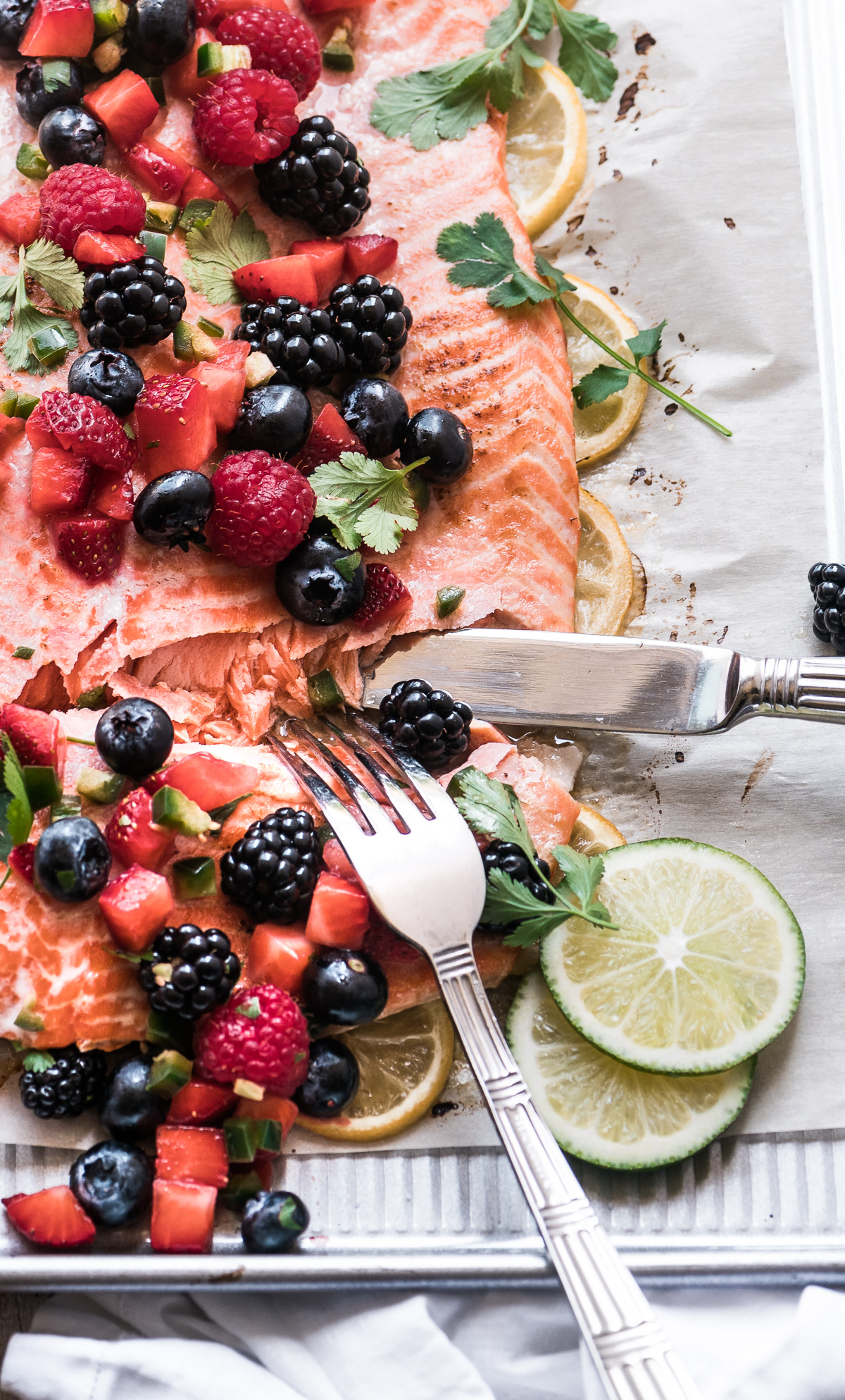 Cutting into a salmon with berry salsa