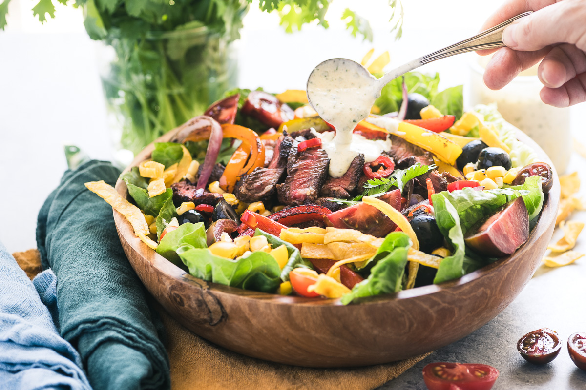 Spooning dressing on a Mexican Steak Fajita Salad