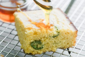 drizzling honey on a piece of honey jalapeño cornbread