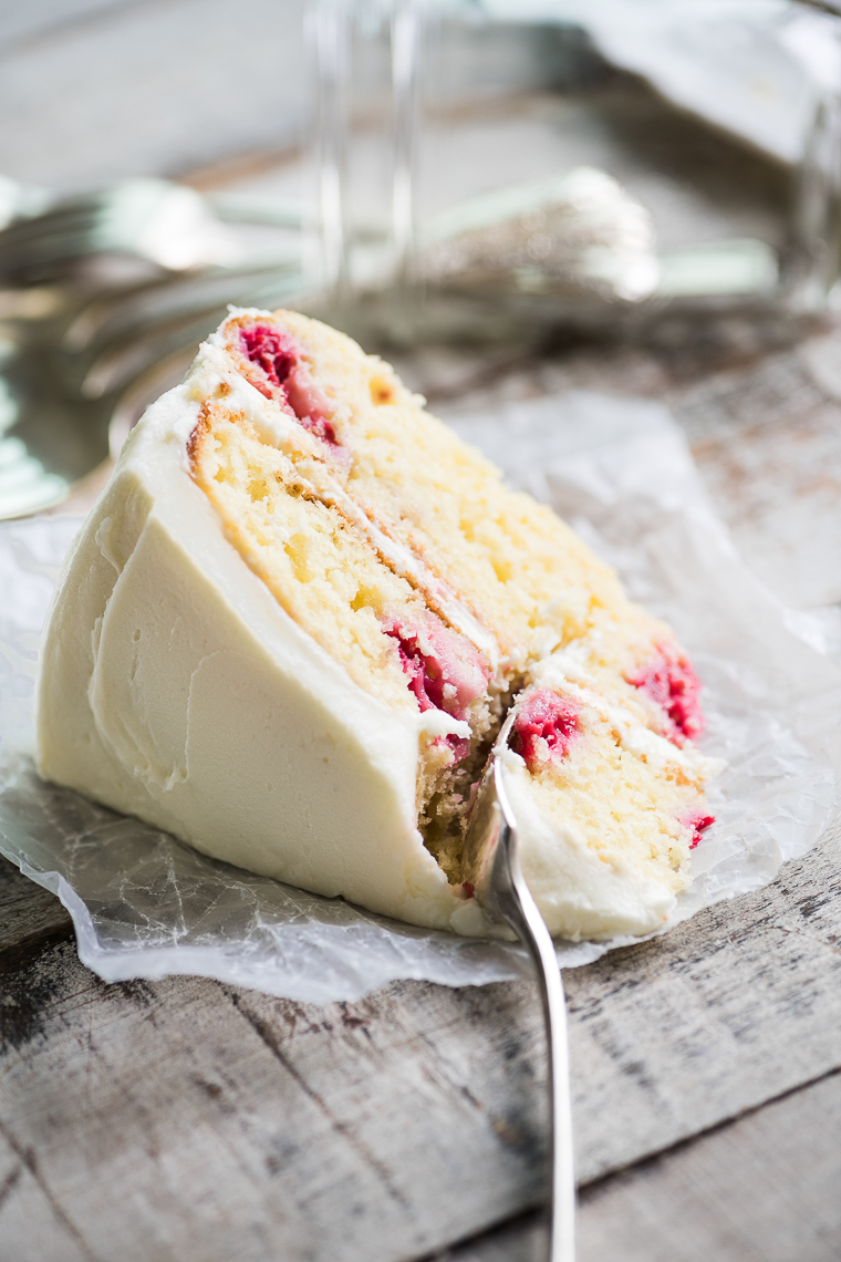 A slice of Raspberry Lemon Tea Cake on a wooden table