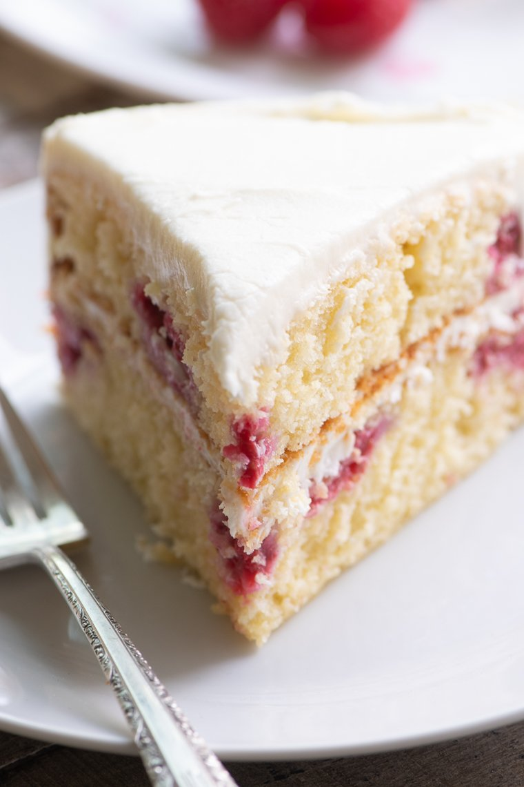 A slice of raspberry lemon cake with lemon buttercream frosting