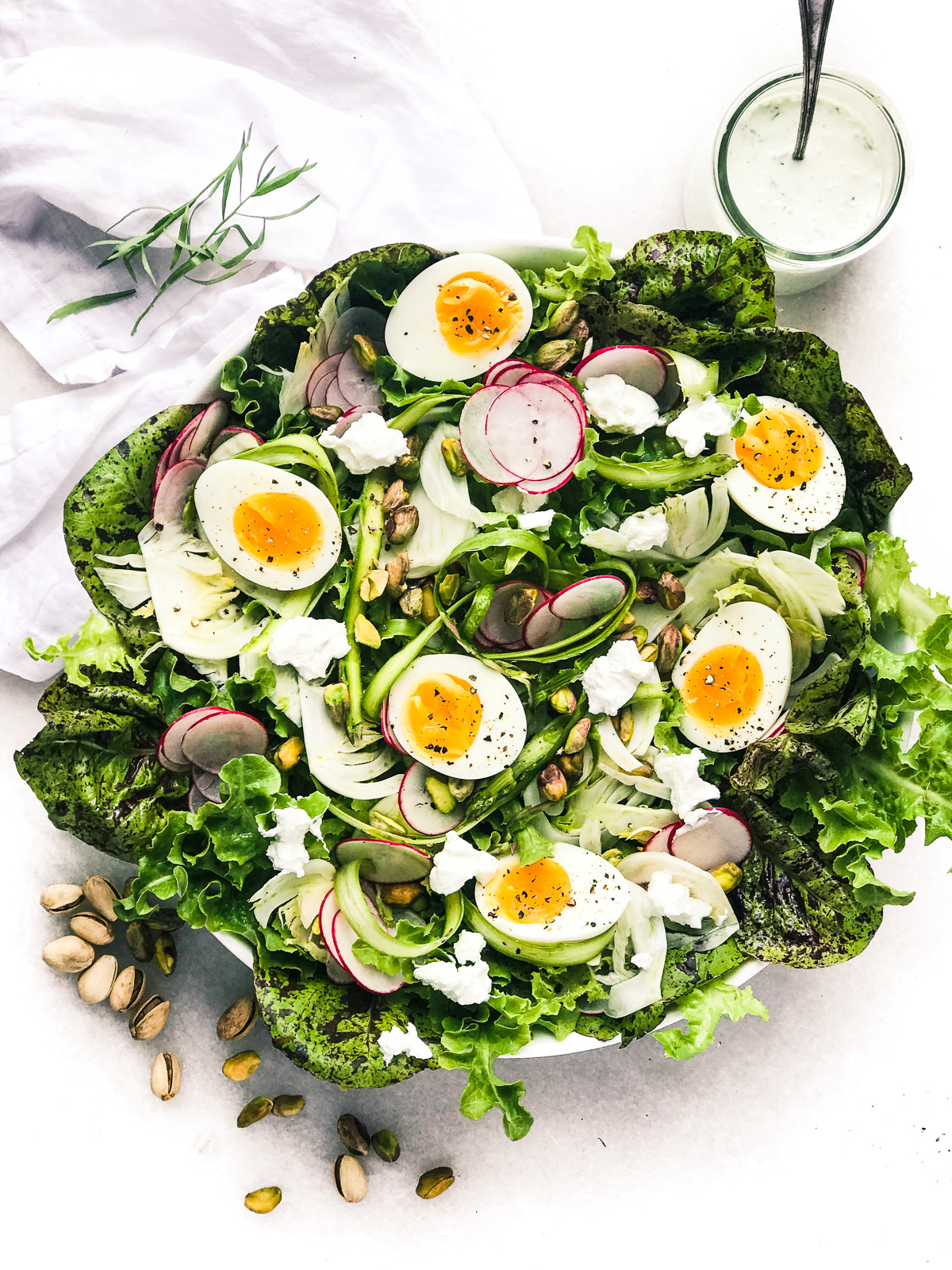 Spring Salad with Creamy Tarragon Vinaigrette on a white marble surface