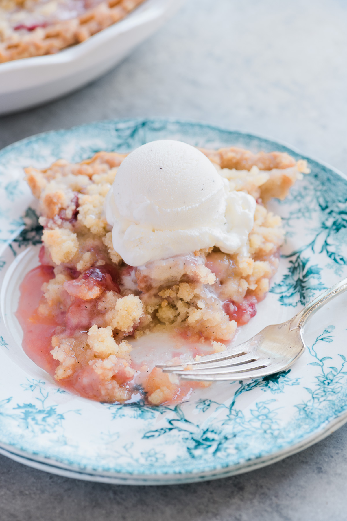A slice of Strawberry Rhubarb Crumble Pie with ice cream