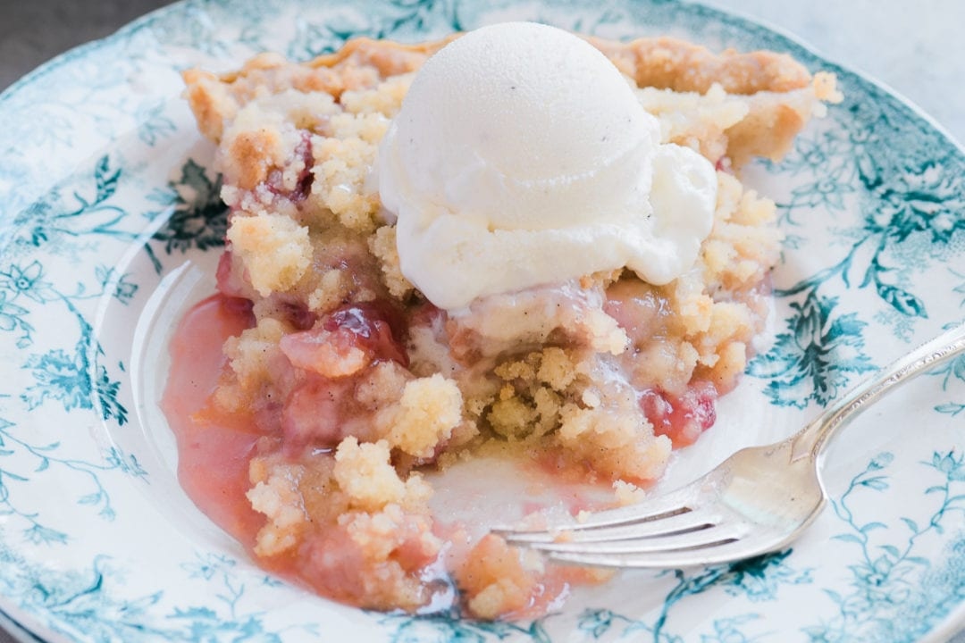 A slice of strawberry rhubarb pie with ice cream on a blue floral plate